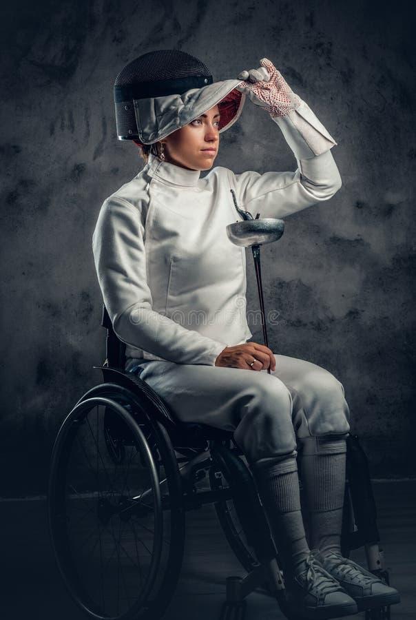 El cercador de sexo femenino en silla de ruedas sostiene la máscara de la seguridad y una espada fotografía de archivo libre de regalías