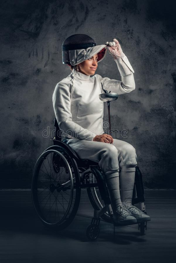 El cercador de sexo femenino en silla de ruedas sostiene la máscara de la seguridad y una espada fotografía de archivo