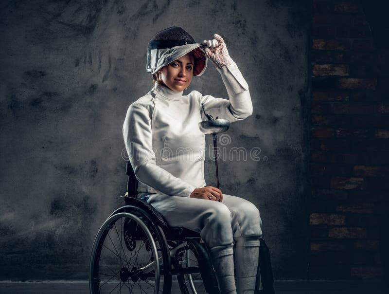 El cercador de sexo femenino en silla de ruedas sostiene la máscara de la seguridad y una espada fotos de archivo libres de regalías