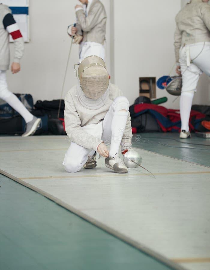 El cercador en el traje blanco con el estoque y la máscara protectora ata cordones fotografía de archivo