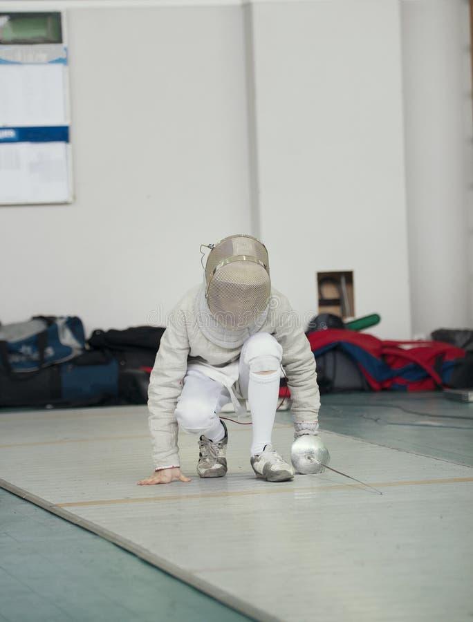 El cercador en el traje blanco con el estoque y la máscara protectora se levanta fotografía de archivo libre de regalías