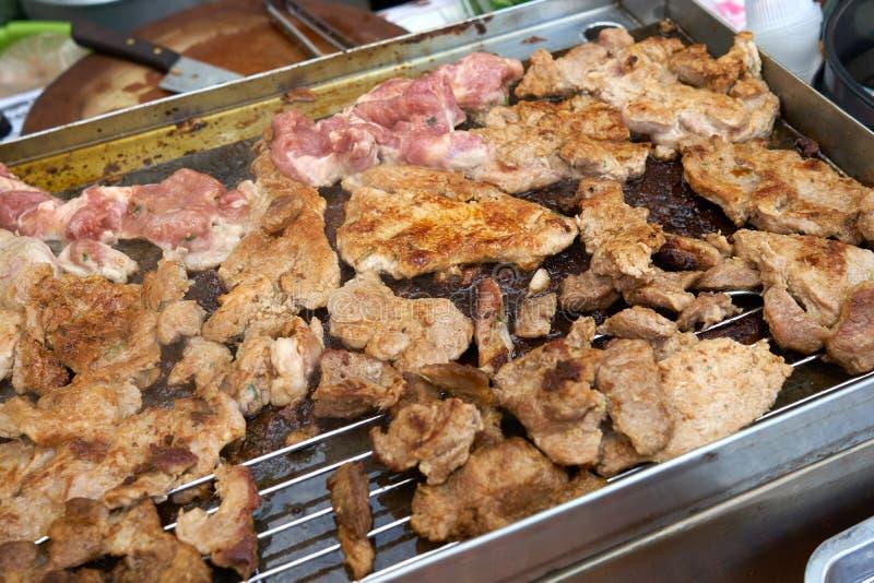 El cerdo asado a la parrilla asado en la placa de acero o la parrilla en el mercado de la comida de la calle de Tailandia es una  foto de archivo