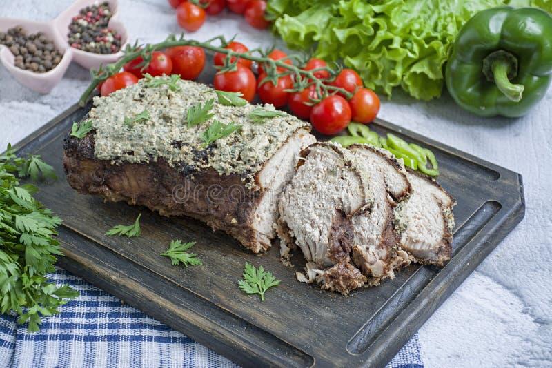El cerdo cocido tajó en una salsa de la nuez y de menta en una tabla de cortar con las hierbas y las verduras frescas Fondo liger imagenes de archivo