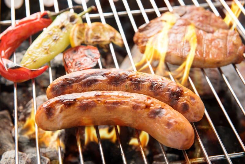El cerdo de la salchicha y el filete de tajada en un Bbq llameante asan a la parrilla imagenes de archivo