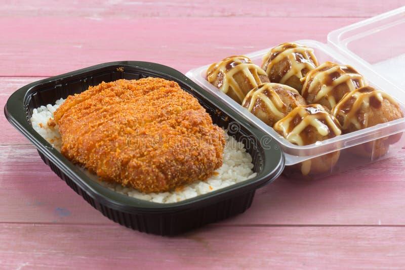 El cerdo frito remató en el tonkatsu y Tako Yaki del arroz en la caja imagen de archivo