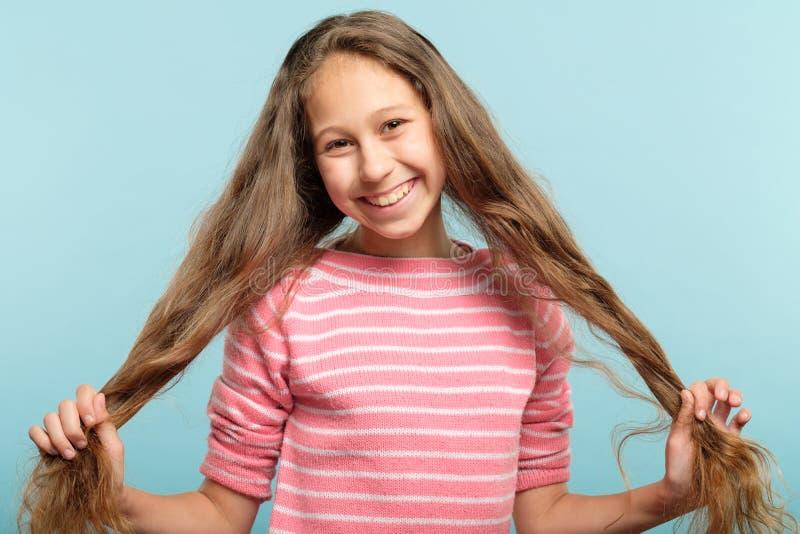 El cerdo sonriente de la muchacha adolescente ata el pelo despreocupado imágenes de archivo libres de regalías