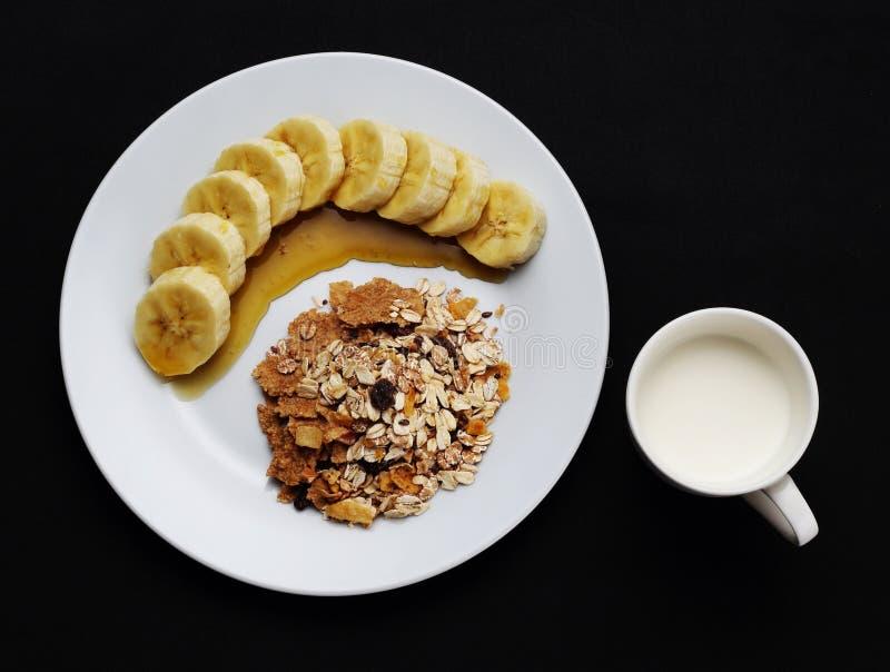 El cereal con el plátano remató con la miel y la leche una taza a la salud foto de archivo
