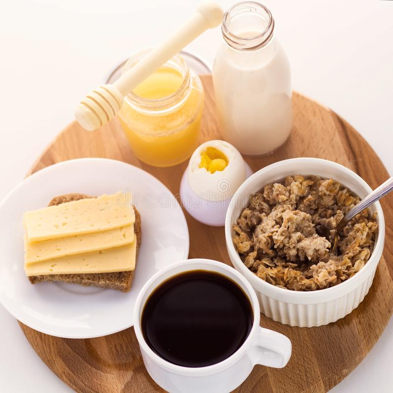 el cereal fresco del desayuno sano, el bocadillo del queso, el huevo duro, la botella de leche, la taza de café y la miel sacuden fotos de archivo