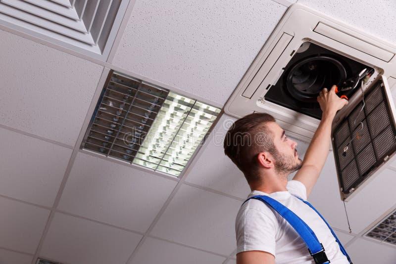 El cerrajero corta los alambres en el sistema de ventilación foto de archivo libre de regalías