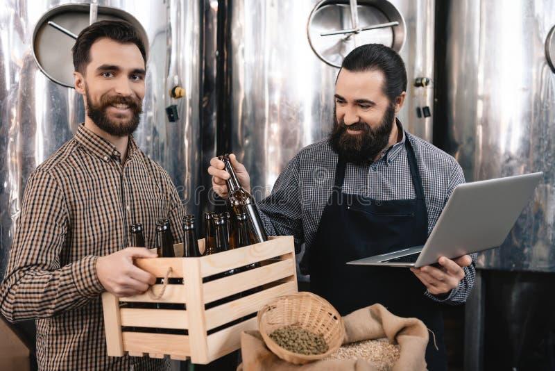 El cervecero barbudo en delantal con el ordenador portátil saca la botella de la caja, que es sostenida por el hombre alegre imagen de archivo libre de regalías