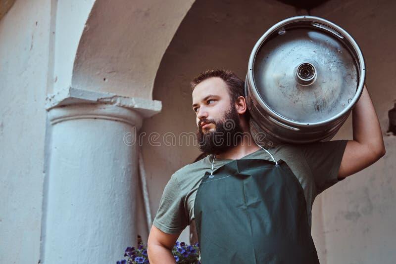 El cervecero en delantal celebra el barril con la cerveza del arte en la fábrica de la cervecería imagenes de archivo