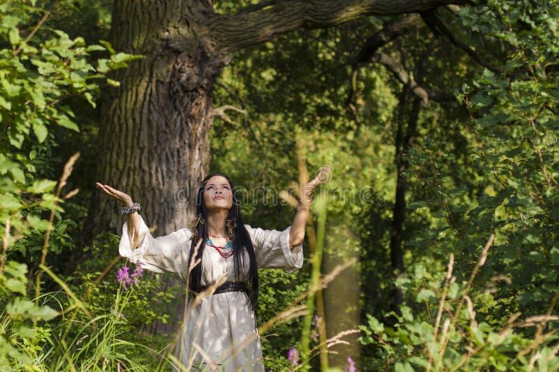 El chamán de la mujer conjura en el bosque fotos de archivo