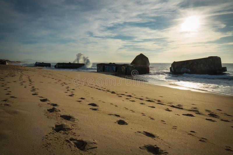 El chapoteo del agua de la onda detrás del blocao en paisaje marino hermoso escénico de la playa arenosa con salpicar agita imagen de archivo libre de regalías