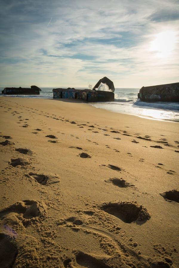 El chapoteo del agua de la onda detrás del blocao en paisaje marino hermoso escénico de la playa arenosa con salpicar agita fotografía de archivo