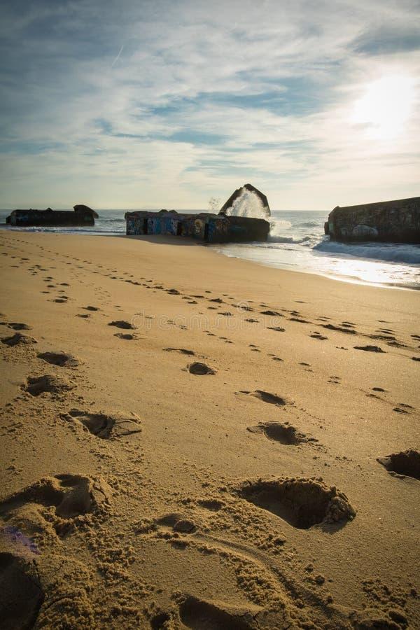 El chapoteo del agua de la onda detrás del blocao en paisaje marino hermoso escénico de la playa arenosa con salpicar agita imagenes de archivo
