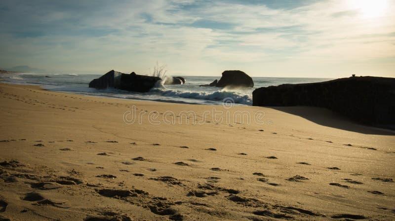 El chapoteo del agua de la onda detrás del blocao en paisaje marino hermoso escénico de la playa arenosa con salpicar agita imágenes de archivo libres de regalías