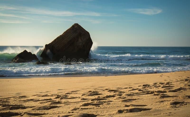 el chapoteo hermoso del agua de la onda detrás del blocao en paisaje marino hermoso escénico de la playa arenosa con salpicar agi imagenes de archivo