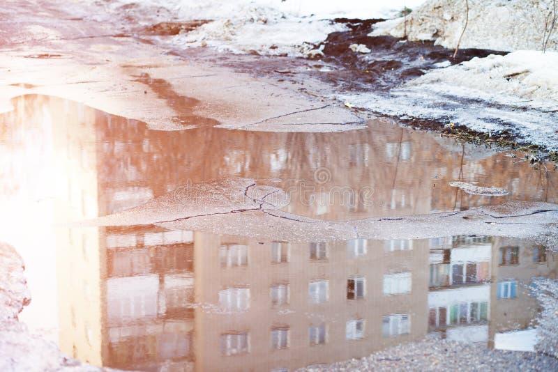 El charco profundo con nieve de los terrones derrite en el camino en la ciudad fotografía de archivo
