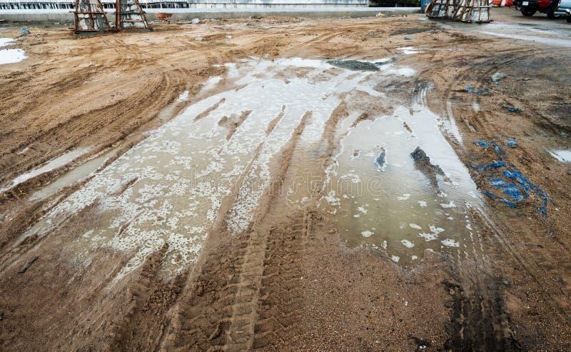 El charco y el fango con el camión ruedan la pista en el emplazamiento de la obra en día lluvioso fotos de archivo libres de regalías