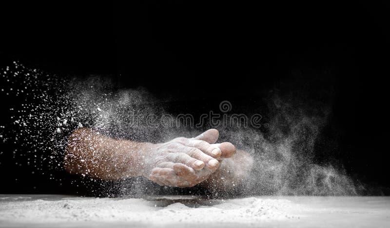 El chef aplaude la mano y el polvo de harina blanca sobre fondo negro fotos de archivo