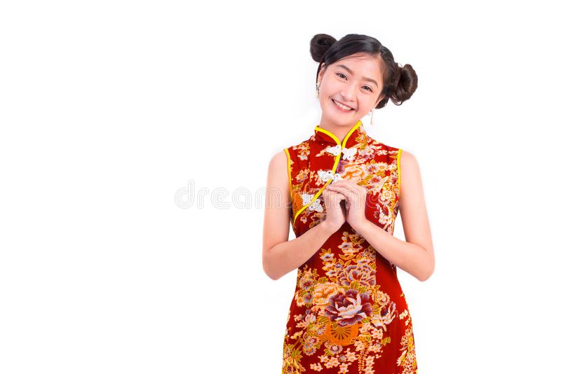 El cheongsam que lleva y la bendición de la mujer asiática joven de la belleza o saludan imágenes de archivo libres de regalías
