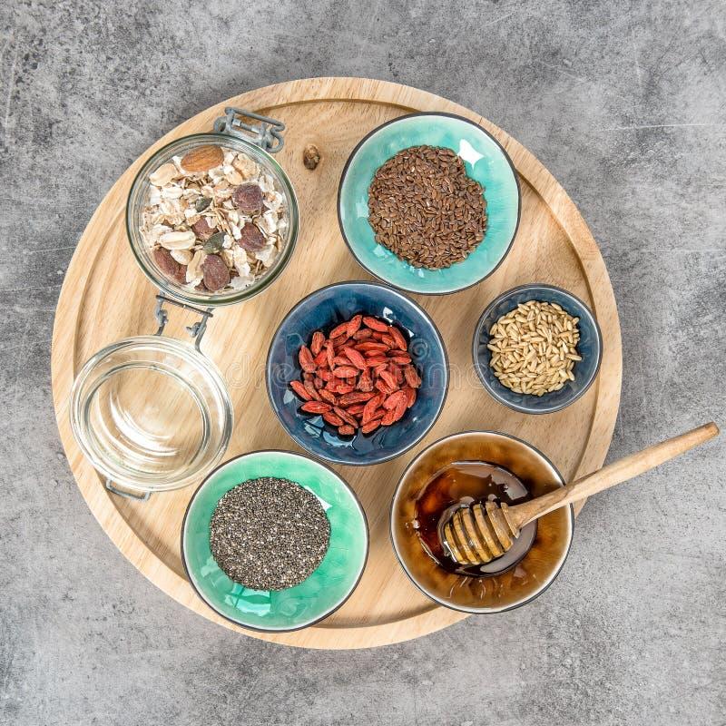 El chia del desayuno del muesli de la harina de avena siembra la miel de la linaza de las bayas del goji imagen de archivo