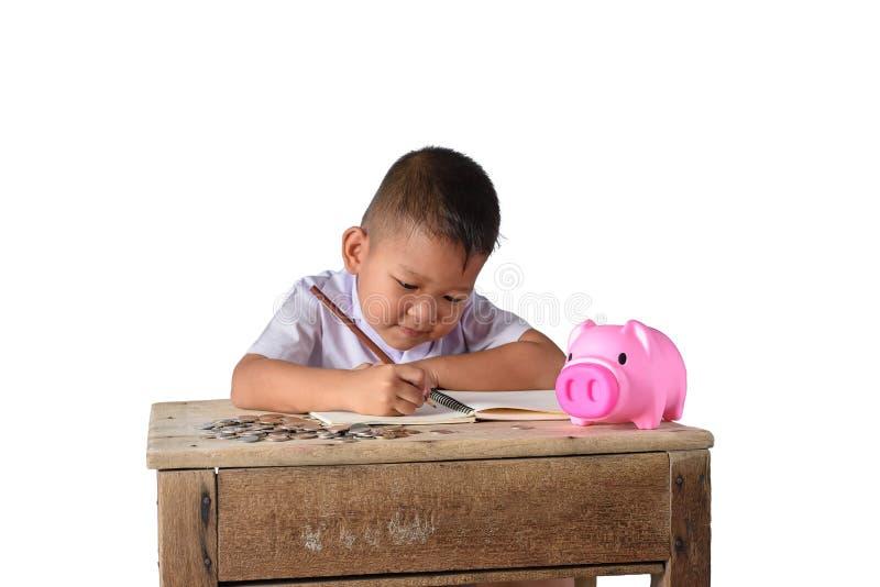 El chico del campo asiático lindo anota recibos y monedas de la renta con la hucha aislada en el fondo blanco fotografía de archivo libre de regalías