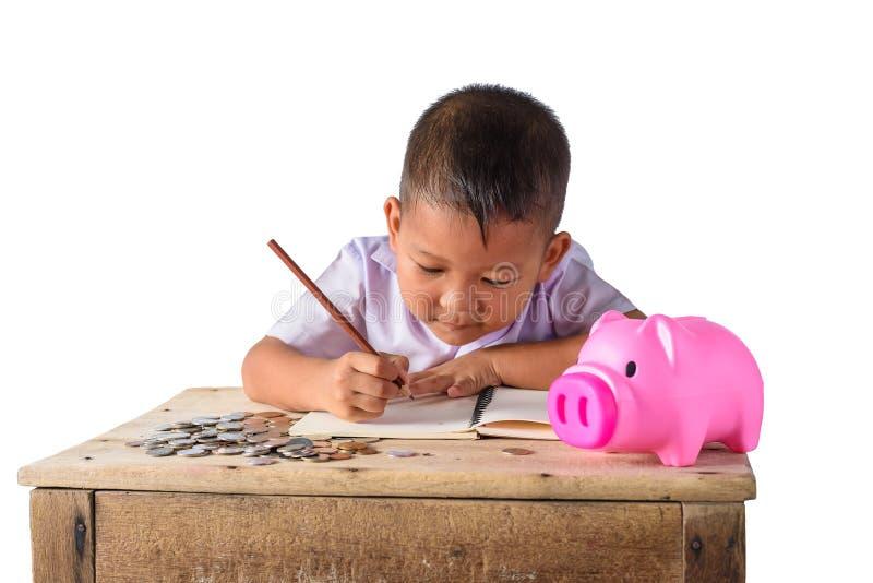 El chico del campo asiático lindo anota recibos y monedas de la renta con la hucha aislada en el fondo blanco imágenes de archivo libres de regalías