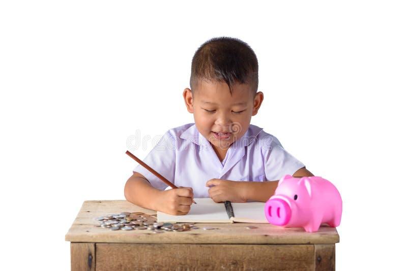 El chico del campo asi?tico lindo anota recibos y monedas de la renta con la hucha aislada en el fondo blanco fotografía de archivo libre de regalías