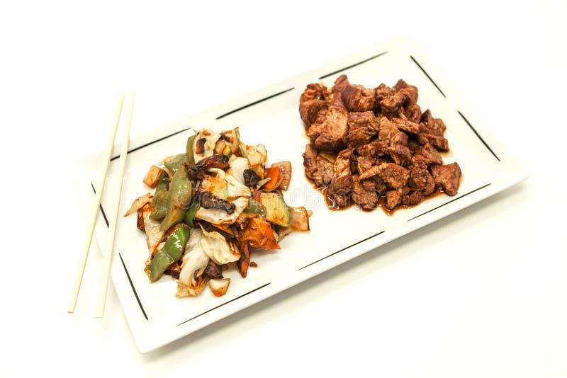 El chino frió la carne de vaca en salsa dulce-amarga y guisó verduras En un fondo blanco foto de archivo