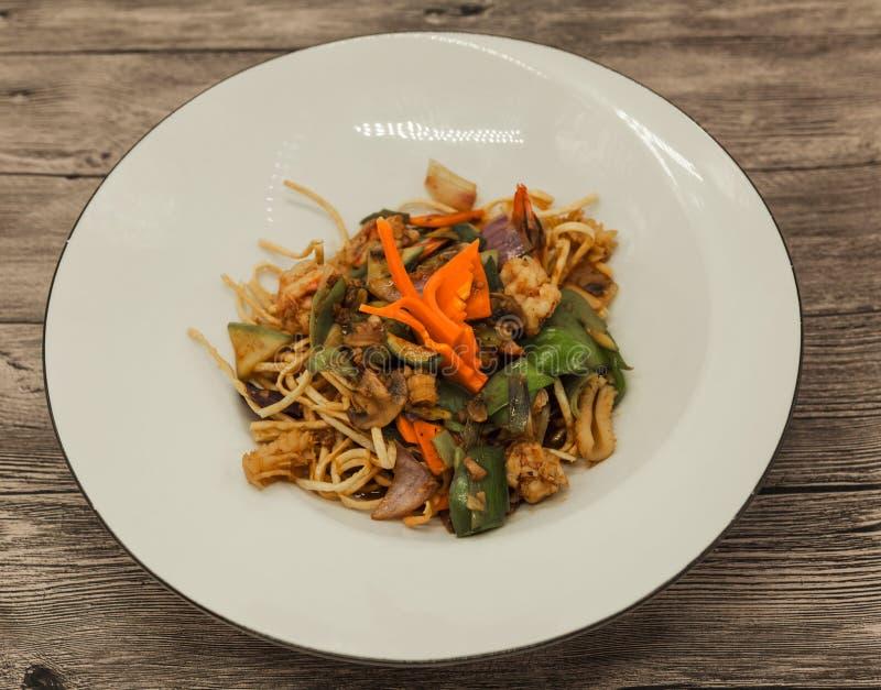 El chino frió los tallarines con calamares, un pulpo y las verduras imagenes de archivo