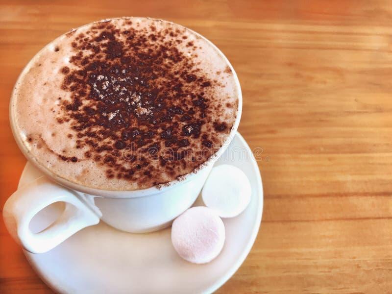El chocolate caliente de la bebida remató por la espuma del Latte de la leche con la melcocha en la taza de cerámica blanca en fo imagen de archivo