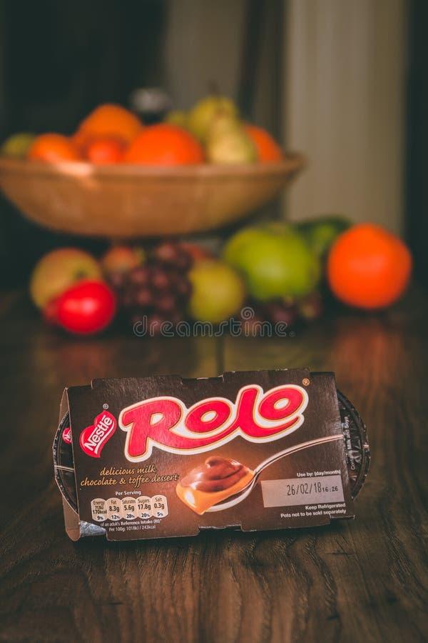 El chocolate con leche y el caramelo de Nestlé Rolo abandonan el envase encima de una tabla de madera con la fruta sana en el fo fotos de archivo