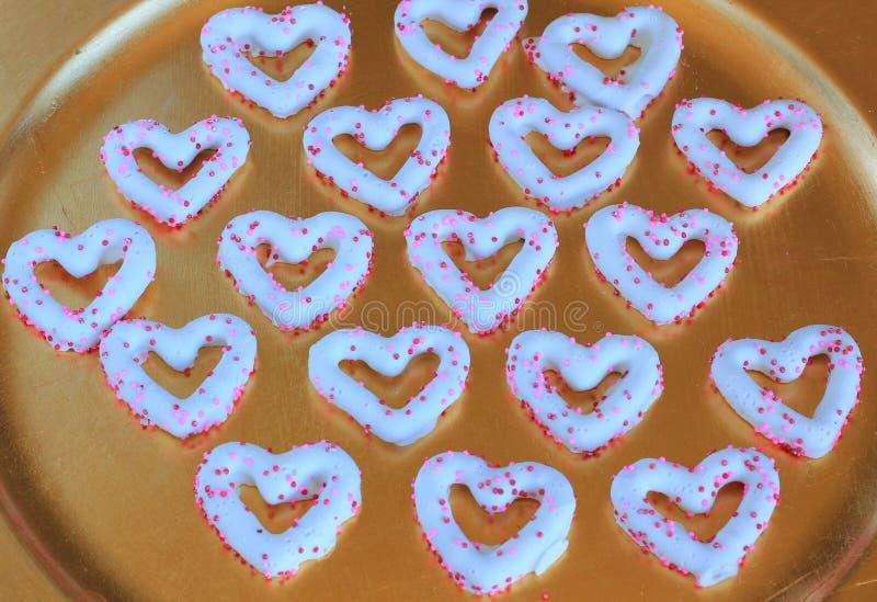 El chocolate del corazón de la tarjeta del día de San Valentín cubrió los pretzeles fotos de archivo