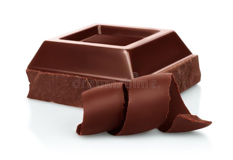 El chocolate junta las piezas con las virutas del chocolate en el fondo blanco fotografía de archivo