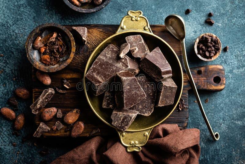 El chocolate oscuro junta las piezas los granos machacado y de cacao Fondo del chocolate foto de archivo libre de regalías