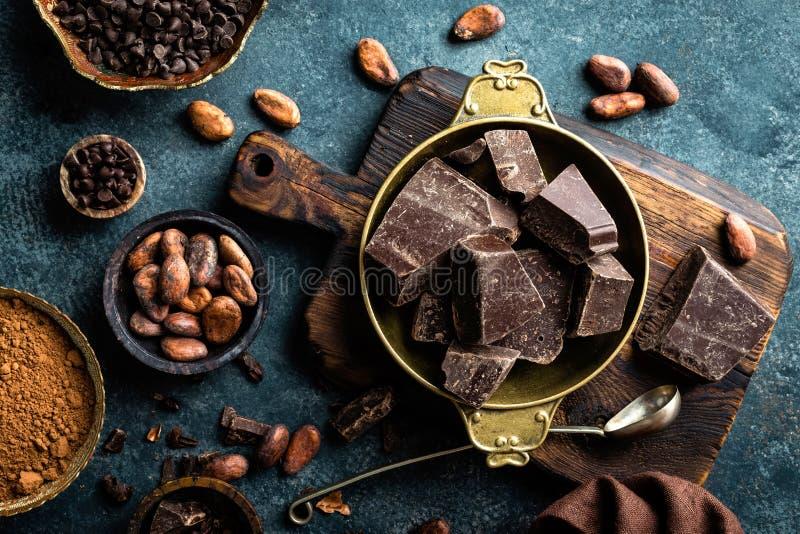 El chocolate oscuro junta las piezas los granos machacado y de cacao Fondo del chocolate fotografía de archivo