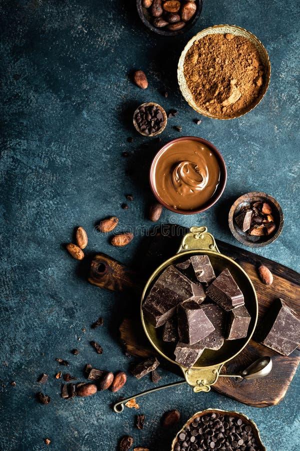 El chocolate oscuro junta las piezas los granos machacado y de cacao Fondo del chocolate fotos de archivo