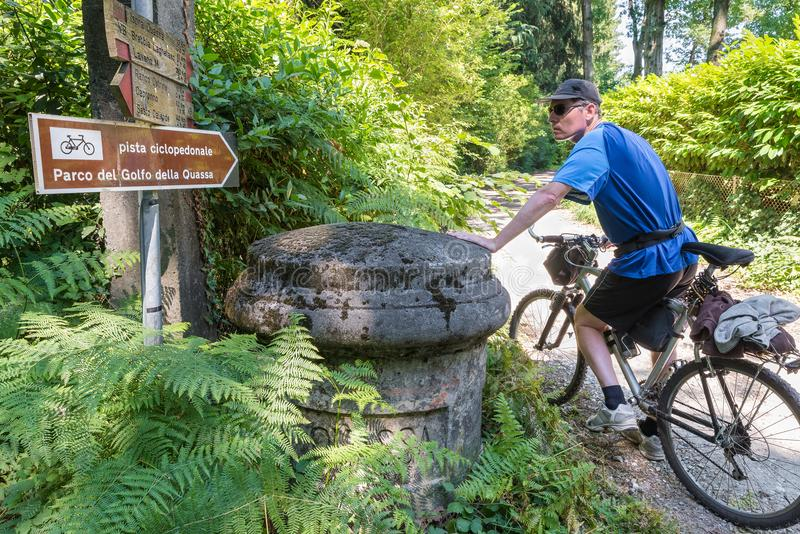 El ciclista, con la bici de montaña en una trayectoria de la suciedad, observa una muestra direccional imagen de archivo