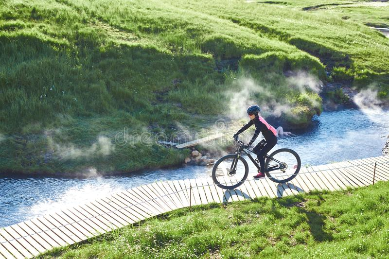 El ciclista de la mujer bikes abajo de la cuesta en el valle del río de Hveragerdi Islandia foto de archivo