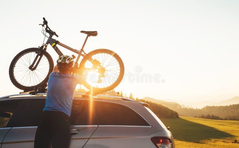 El ciclista del hombre veared en ropa de ciclo y casco protector instala su bici de montaña en el tejado del coche imagen de archivo
