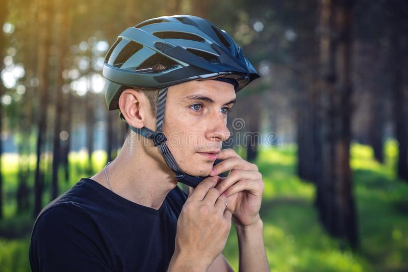 El ciclista está llevando un casco de los deportes en su cabeza en el fondo de la naturaleza verde Protección durante Biking de m imagen de archivo