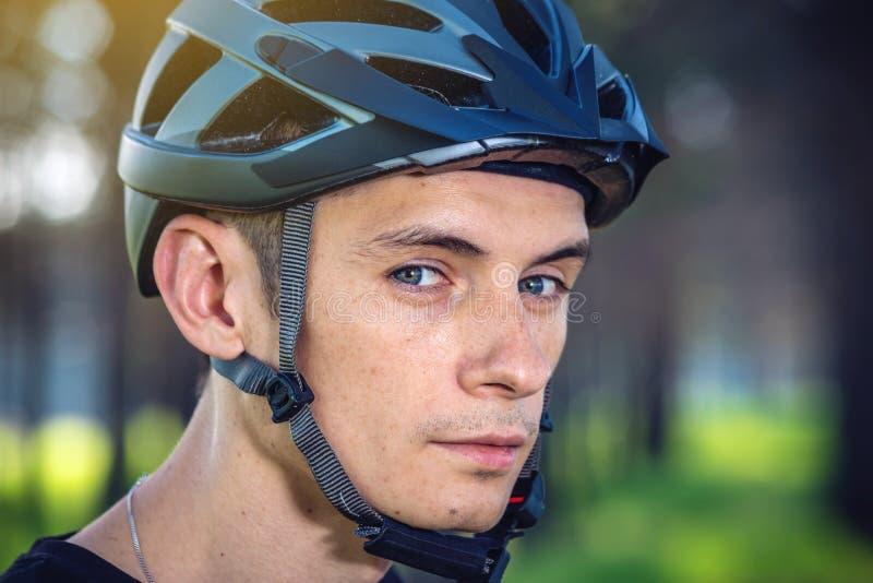El ciclista está llevando un casco de los deportes en su cabeza en el fondo de la naturaleza verde Protección durante Biking de m imagenes de archivo
