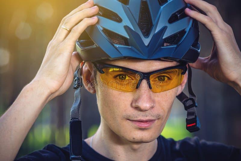 El ciclista está llevando un casco de los deportes en su cabeza en el fondo de la naturaleza verde Protección durante Biking de m fotografía de archivo libre de regalías