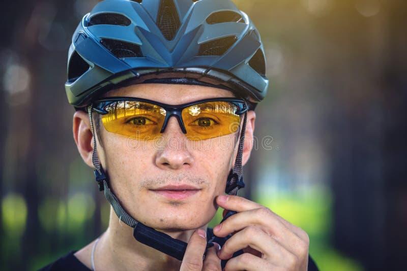 El ciclista está llevando un casco de los deportes en su cabeza en el fondo de la naturaleza verde Protección durante Biking de m imagen de archivo libre de regalías
