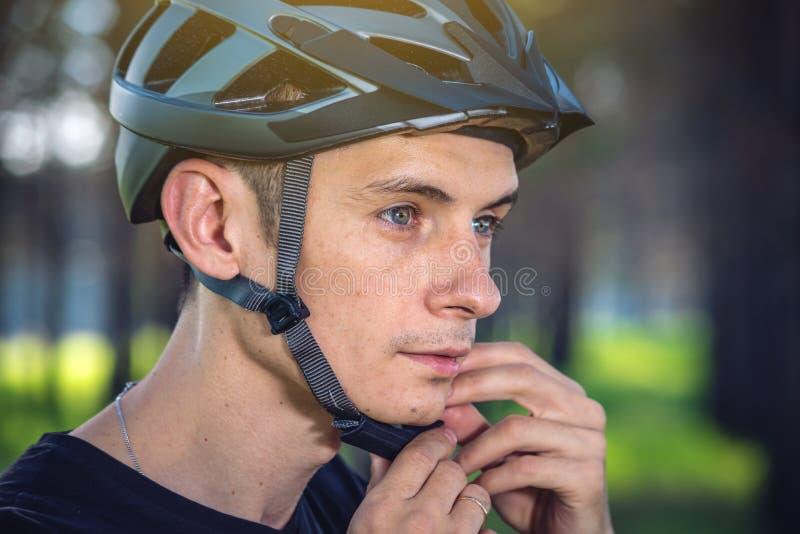El ciclista está llevando un casco de los deportes en su cabeza en el fondo de la naturaleza verde Protección durante Biking de m fotografía de archivo