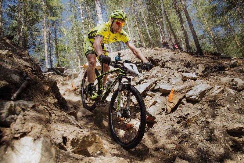 el ciclista masculino del atleta monta abajo de la montaña en piedras imágenes de archivo libres de regalías