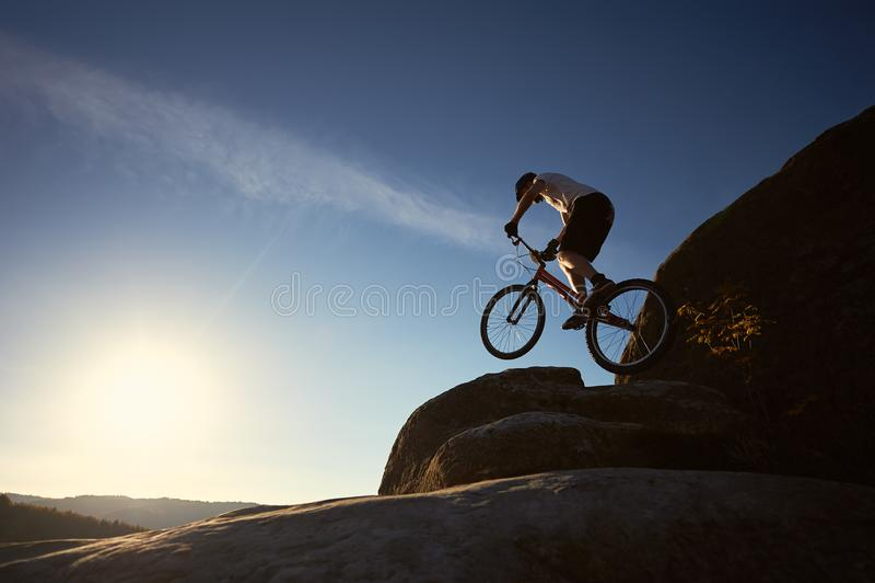 El ciclista profesional del deportista salta en la bici de ensayo en el canto rodado fotos de archivo