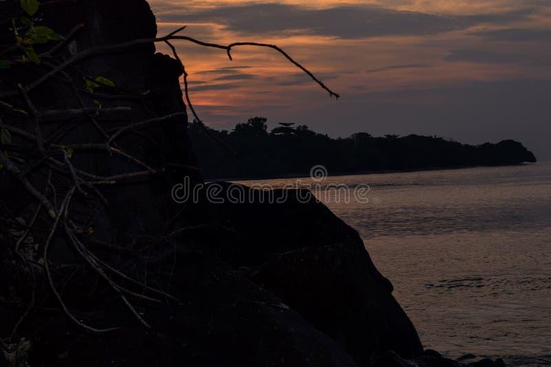 El cielo anaranjado sobre él con la reflexión de oro del sol impresionante en calma agita como fondo Opinión asombrosa de la pues foto de archivo libre de regalías