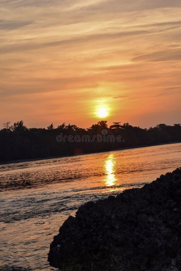 El cielo anaranjado sobre él con la reflexión de oro del sol impresionante en calma agita como fondo Opinión asombrosa de la pues imágenes de archivo libres de regalías